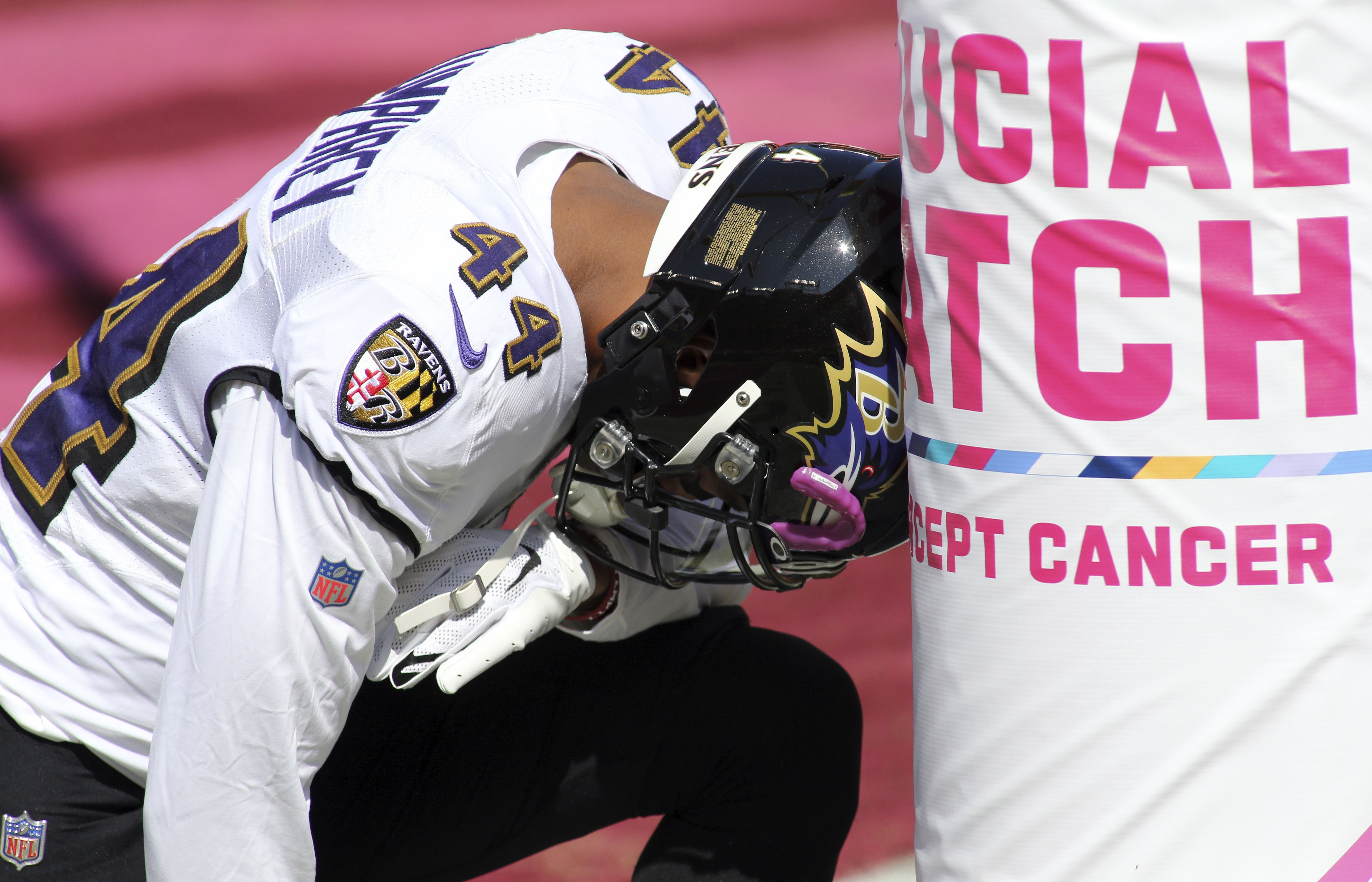 Baltimore Ravens cornerback Marlon Humphrey (44) kneels in from of an NFL Breast Cancer Awareness sign before an NFL match against the Baltimore Ravens and the Washington Football Team , Sunday, Oct. 4, 2020 in Landover, Md. (AP Photo/Daniel Kucin Jr.)
