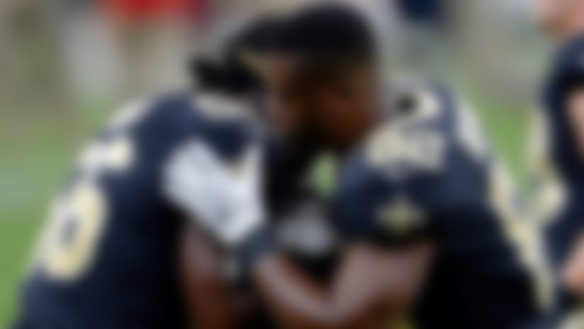 New Orleans Saints linebacker Demario Davis (56) and tight end Benjamin Watson (82) kneel and embrace before an NFL football game against the Tampa Bay Buccaneers in New Orleans, Sunday, Sept. 9, 2018. (AP Photo/Bill Feig)
