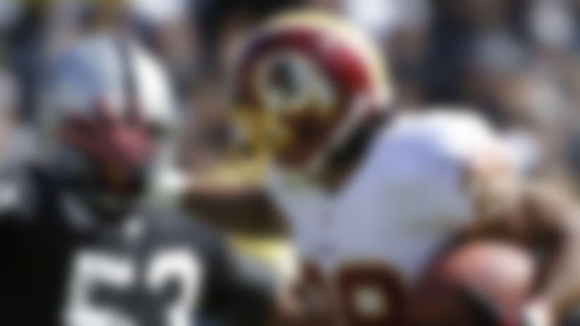 Washington Redskins running back Roy Helu stiffarms Oakland Raiders linebacker Nick Roach. (AP Photo/Marcio Jose Sanchez)