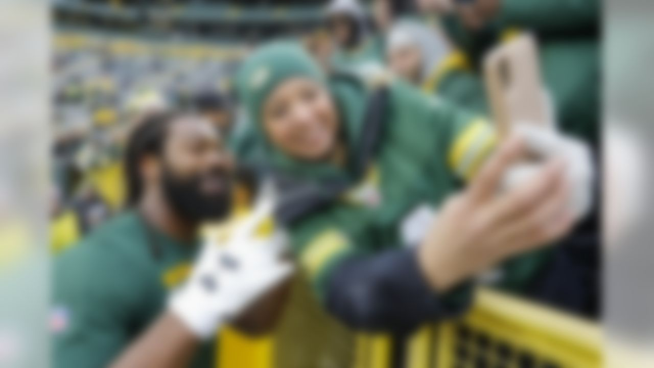 Green Bay Packers' Za'Darius Smith smiles for a selfie with a fan before an NFL football game against the Carolina Panthers Sunday, Nov. 10, 2019, in Green Bay, Wis. (AP Photo/Mike Roemer)