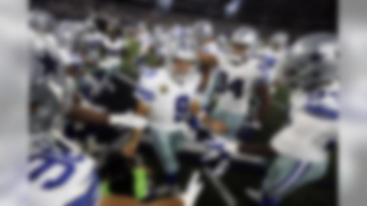 Dallas Cowboys quarterback Tony Romo (9) is greeted by the team before an NFL football game against the New York Giants Sunday, Sept. 13, 2015, in Arlington, Texas. (AP Photo/Brandon Wade)