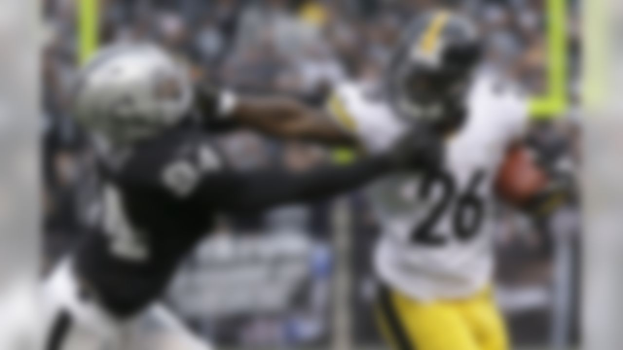 Pittsburgh Steelers running back Le'Veon Bell (26) stiff arms Oakland Raiders outside linebacker Kevin Burnett during the fourth quarter of an NFL football game in Oakland, Calif., Sunday, Oct. 27, 2013. The Raiders won 21-18. (AP Photo/Marcio Jose Sanchez)