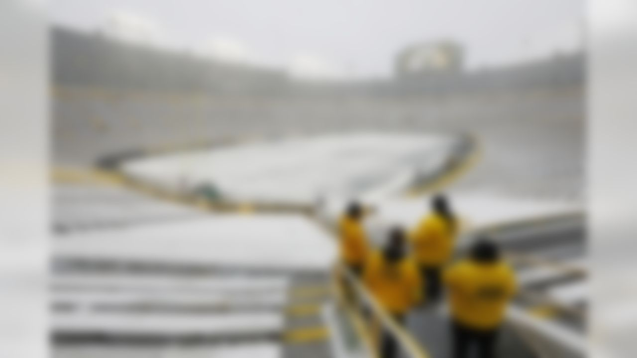 Event staff look out at a snow covered Lambeau Field before an NFL football game between the Green Bay Packers and the Arizona Cardinals on Sunday, Dec. 2, 2018, in Green Bay, Wis. (AP Photo/Mike Roemer)