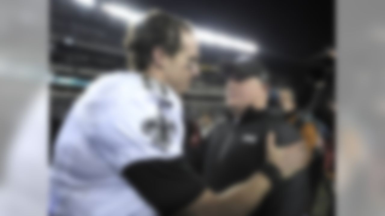 Philadelphia Eagles head coach Chip Kelly, right, meets with New Orleans Saints' Drew Brees after an NFL wild-card playoff football game, Saturday, Jan. 4, 2014, in Philadelphia. New Orleans won 26-24. (AP Photo/Michael Perez)