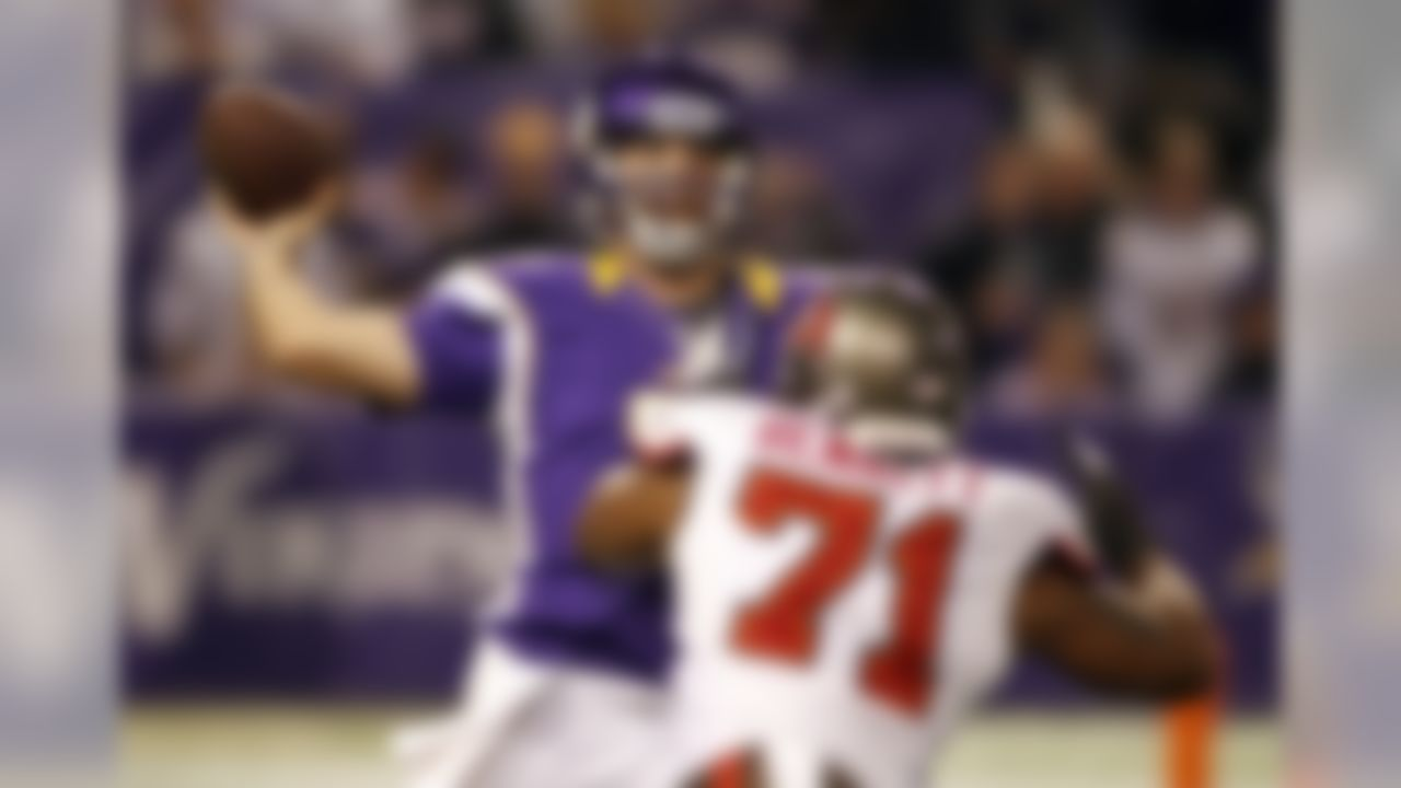Minnesota Vikings quarterback Christian Ponder, left, throws a pass over Tampa Bay Buccaneers defensive end Michael Bennett during the first half of an NFL football game Thursday, Oct. 25, 2012, in Minneapolis. (AP Photo/Andy King)