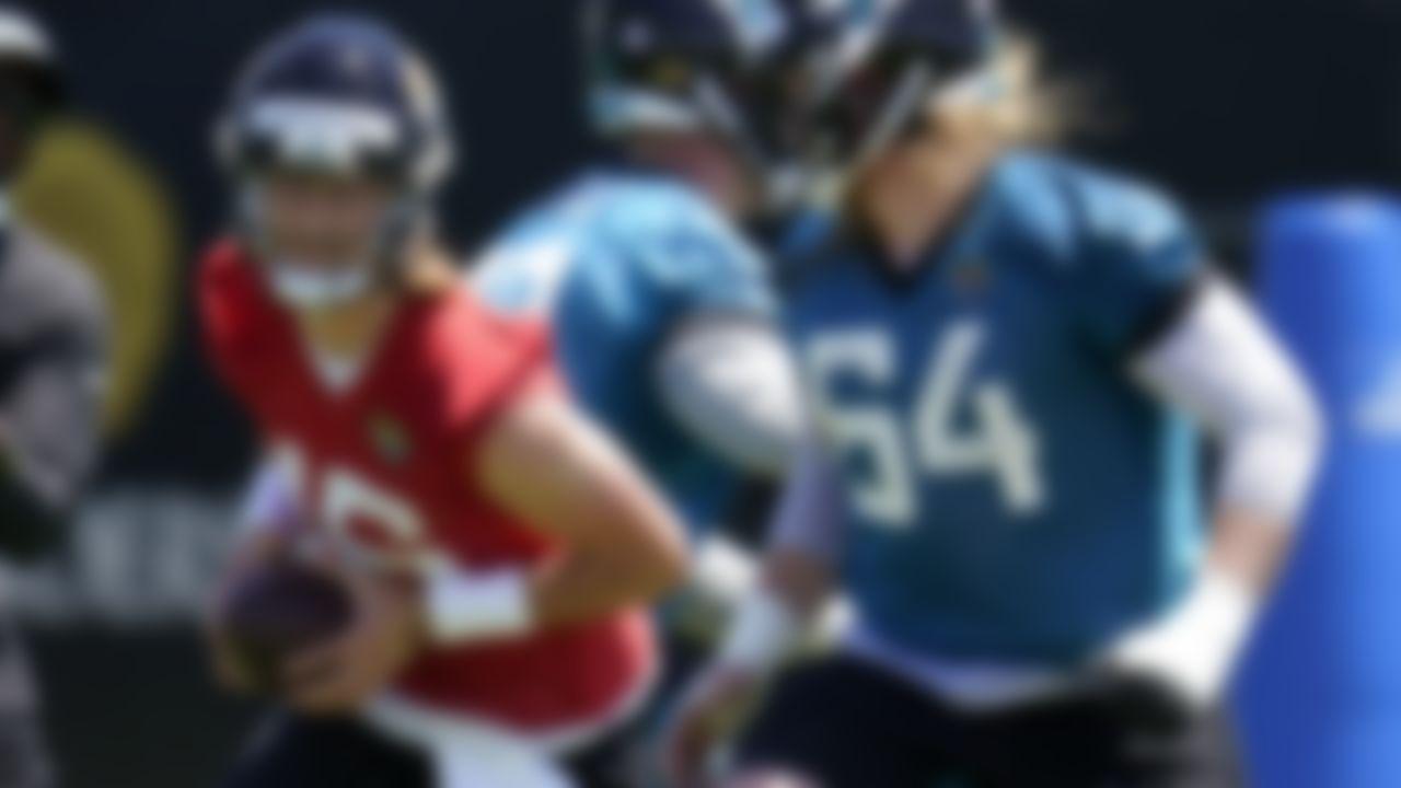 Jacksonville Jaguars quarterback Trevor Lawrence, left, runs a drill as offensive linemen Walker Little, center, and Austen Pleasants (64) block during an NFL football rookie minicamp, Saturday, May 15, 2021, in Jacksonville, Fla.