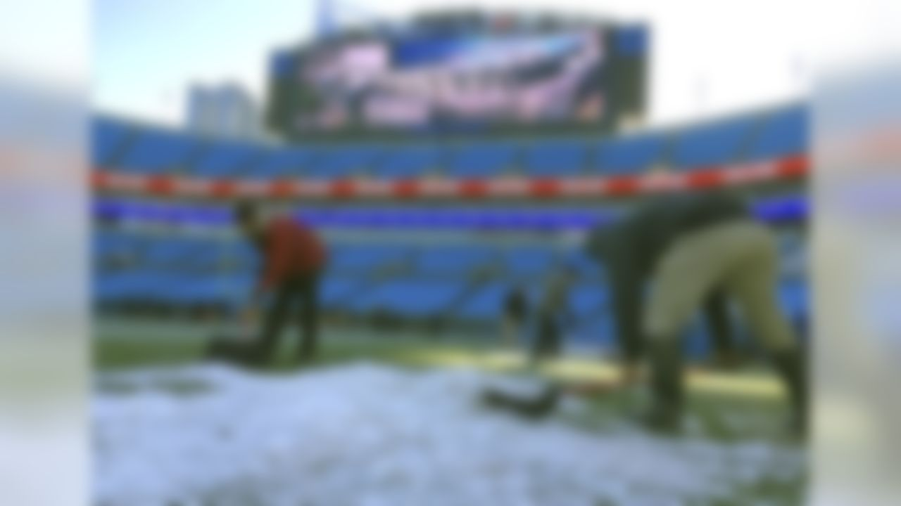 Members of the grounds crew remove ice from the sidelines before an NFL football game between the Carolina Panthers and the Minnesota Vikings in Charlotte, N.C., Sunday, Dec. 10, 2017. (AP Photo/Chuck Burton)