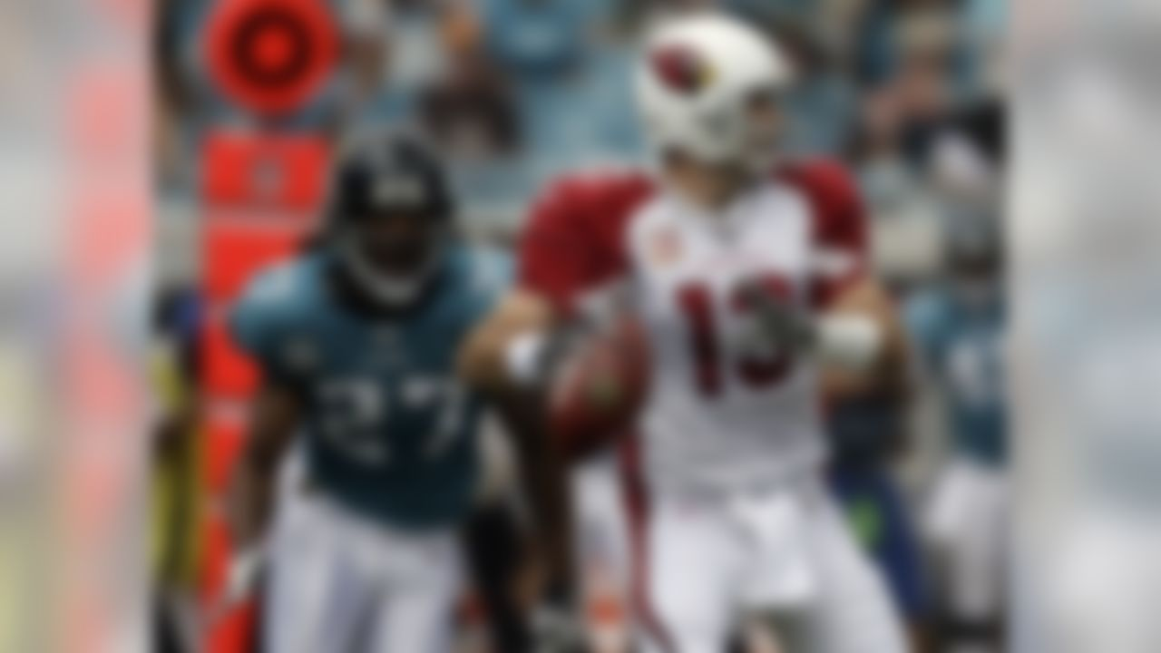 Arizona Cardinals quarterback Kurt Warner (13) gets off a pass just before being hit by Jacksonville Jaguars cornerback Rashean Mathis (27) in the first half of an NFL football game in Jacksonville, Fla., Sunday, Sept. 20, 2009. (AP Photo/John Raoux)