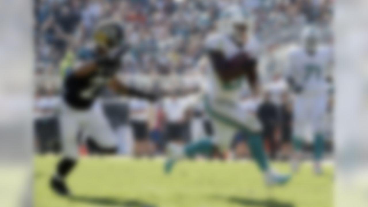 Miami Dolphins running back Lamar Miller, front right, runs past Jacksonville Jaguars cornerback Dwayne Gratz (27) for a 41-yard gain during the second half of an NFL football game in Jacksonville, Fla., Sunday, Oct. 26, 2014. (AP Photo/Phelan M. Ebenhack)
