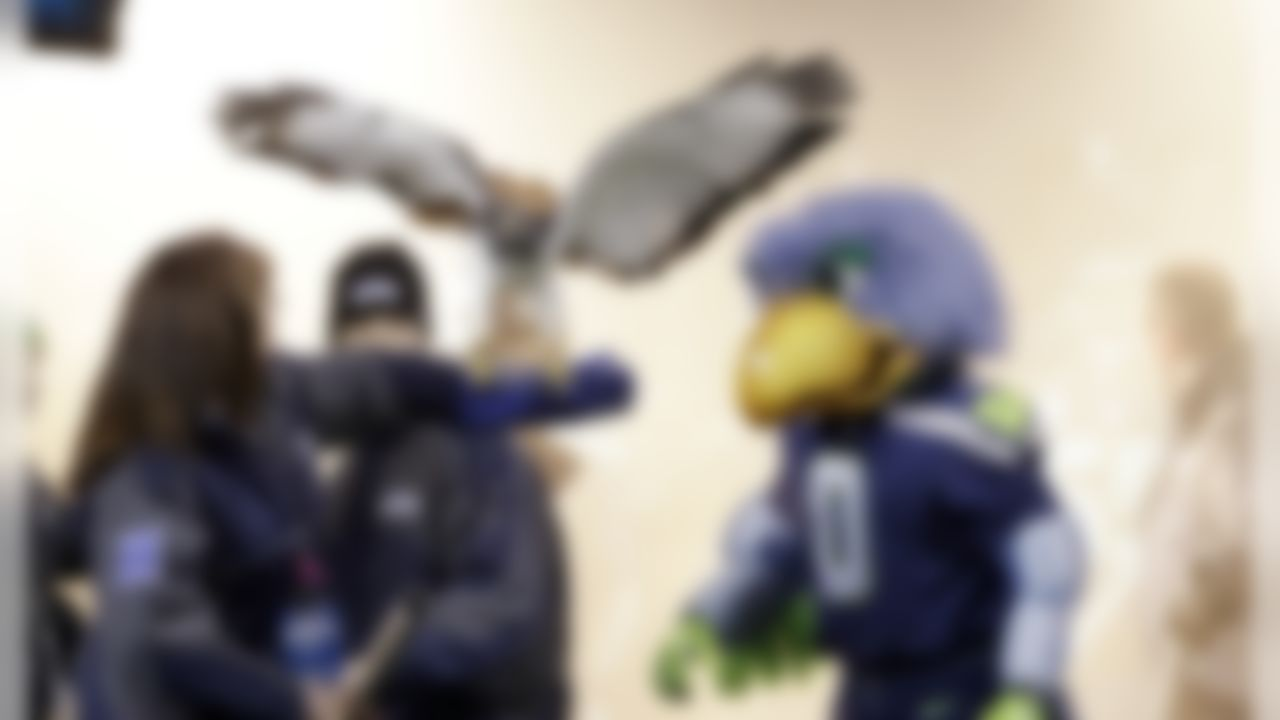 """""""Taima,"""" an auger hawk, flaps her wings while standing on the arm of her handler and next to the Seattle Seahawks' mascot """"Blitz,"""" as both wait to make their entrance during player introductions before an NFL football game against the New Orleans Saints, Monday, Dec. 2, 2013, in Seattle. (AP Photo/Elaine Thompson)"""