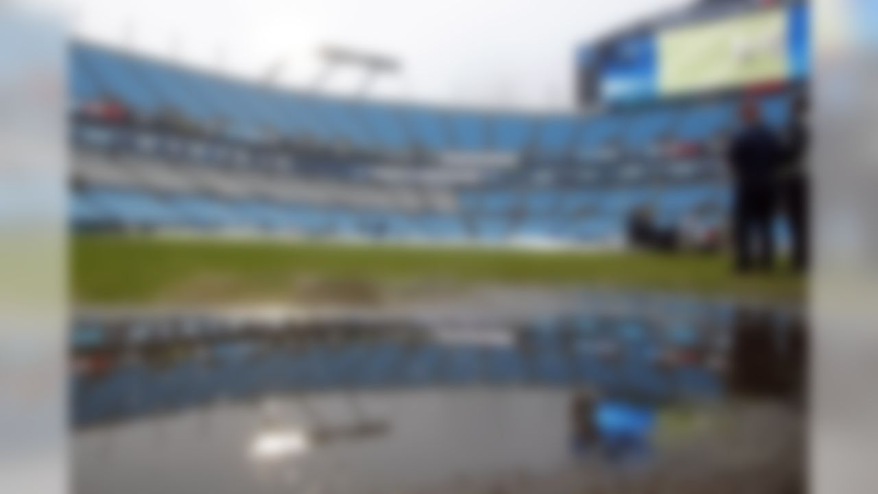 Workers remove a rain cover from the playing field prior to an NFL football game between the Carolina Panthers and the Washington Redskins in Charlotte, N.C., Sunday, Dec. 1, 2019. (AP Photo/Brian Blanco)