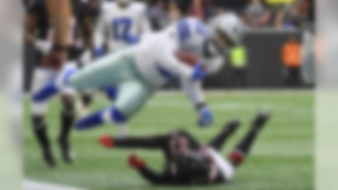 Dallas Cowboys running back Ezekiel Elliott (21) is tripped up by Atlanta Falcons strong safety Damontae Kazee (27) during the first half of an NFL football game, Sunday, Nov. 18, 2018, in Atlanta. (AP Photo/Danny Karnik)