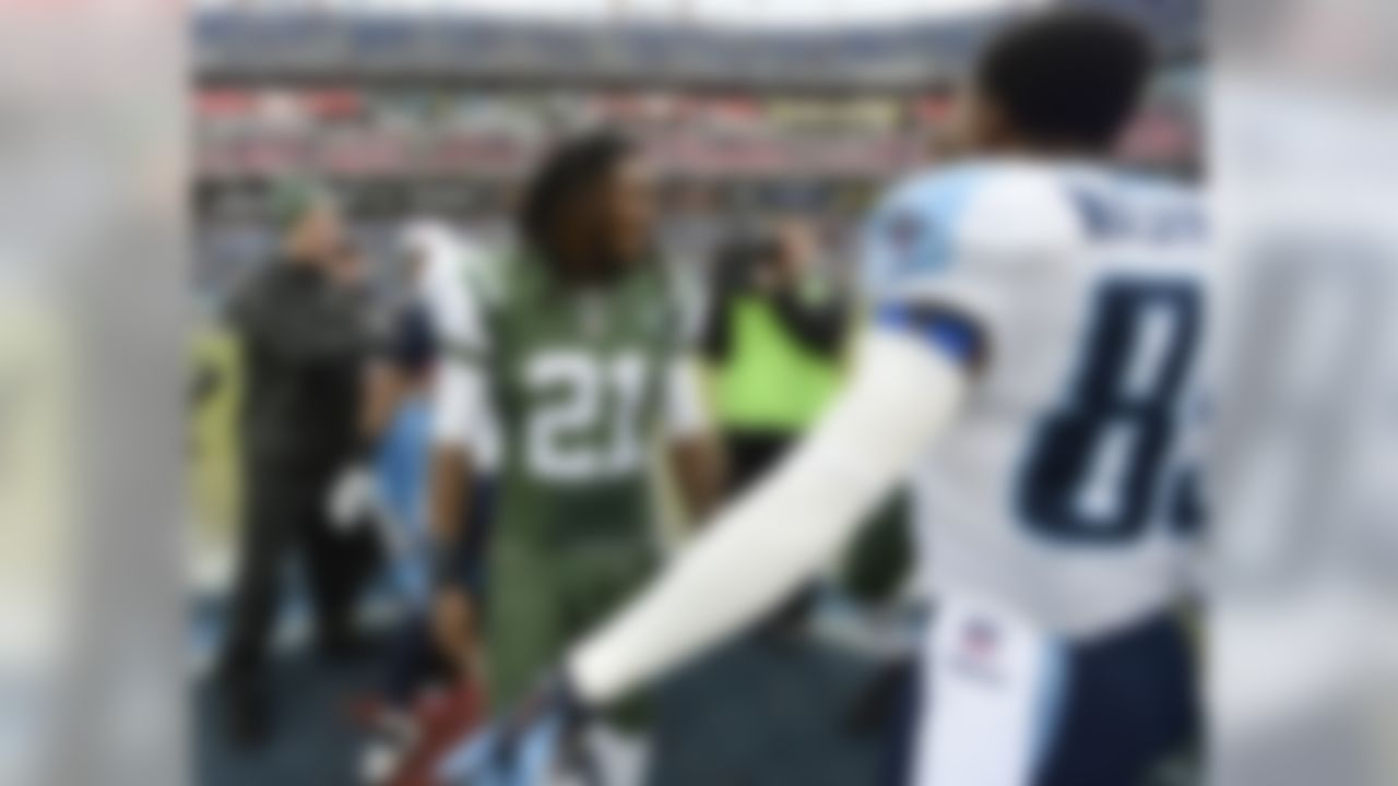 New York Jets running back Chris Johnson (21) talks with Tennessee Titans wide receiver Nate Washington (85) before an NFL football game Sunday, Dec. 14, 2014, in Nashville, Tenn. Johnson is facing his former Titans teammates for the first time Sunday. (AP Photo/Mark Zaleski)