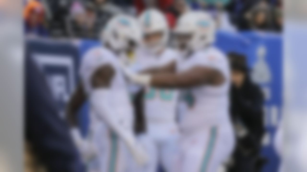 Miami Dolphins wide receiver DeVante Parker, left, celebrates with teammates after scoring a touchdown against the New York Giants during the second quarter of an NFL football game, Sunday, Dec. 15, 2019, in East Rutherford, N.J. (AP Photo/Seth Wenig)