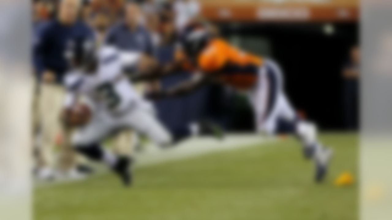 Seattle Seahawks quarterback Russell Wilson (3) is pushed out of bounds by Denver Broncos outside linebacker Nate Irving (56) during the first half of an NFL preseason football game, Thursday, Aug. 7, 2014, in Denver. (AP Photo/Joe Mahoney)