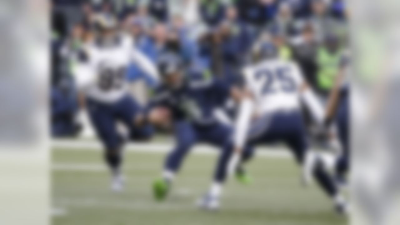 Seattle Seahawks quarterback Russell Wilson (3) scrambles before being tackled by St. Louis Rams' Aaron Donald (99) and T.J. McDonald (25) in the first half of an NFL football game, Sunday, Dec. 28, 2014, in Seattle. (AP Photo/Elaine Thompson)