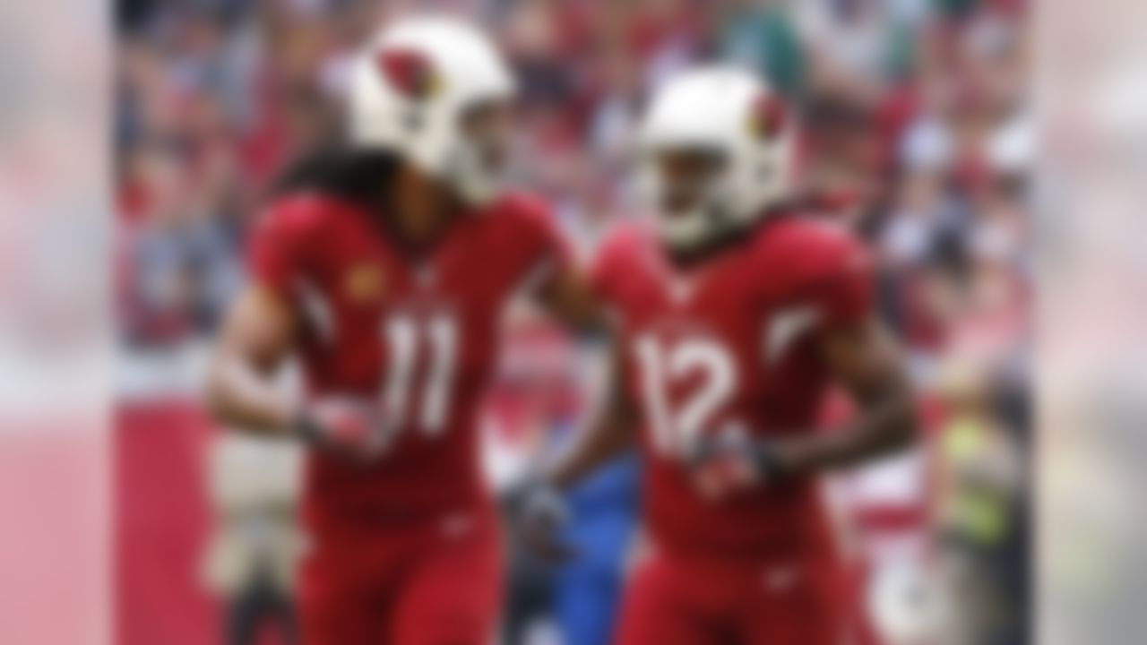 Arizona Cardinals wide receiver Larry Fitzgerald (11) points to the Rams players after a scuffle as he runs to the sidelines with teammate Andre Roberts (12) during the first half of an NFL football game, Sunday, Dec. 8, 2013, in Glendale, Ariz. (AP Photo/Ross D. Franklin)
