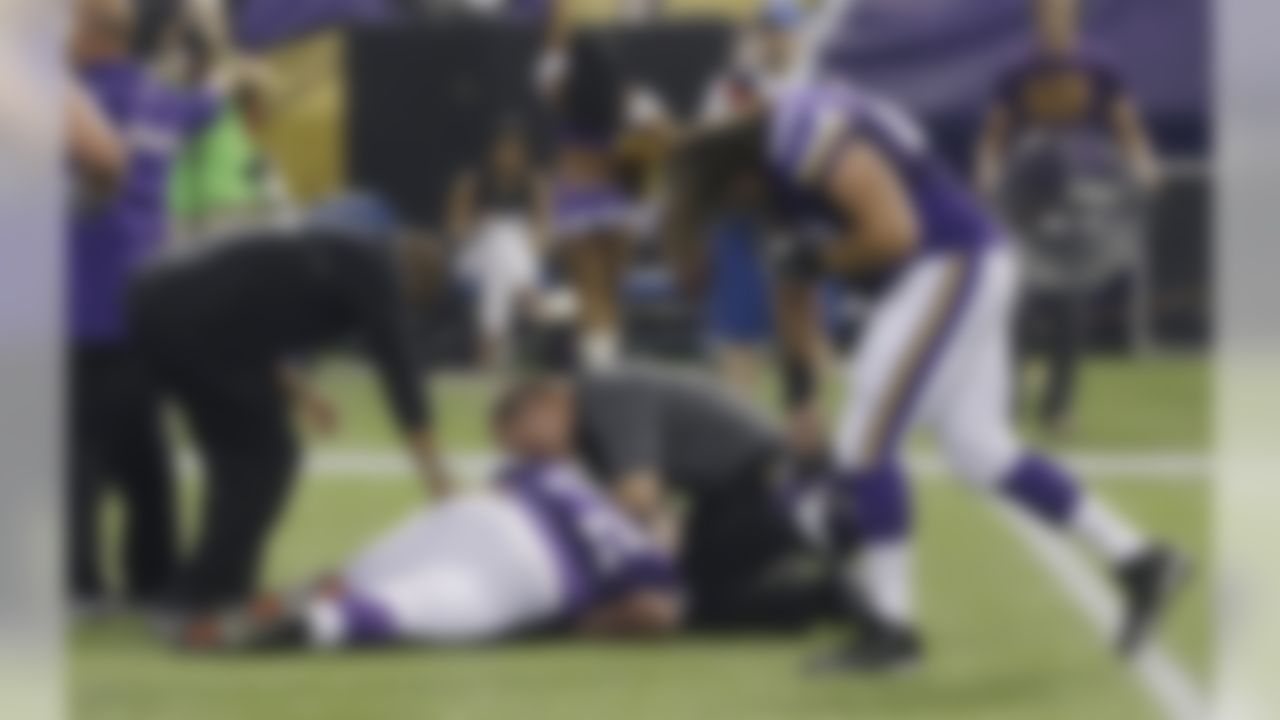 Minnesota Vikings offensive guard Jeff Baca, right, reacts as trainers assist injured Minnesota Vikings guard Seth Olsen, center, during the first half of an NFL preseason football game against the Tennessee Titans Thursday, Aug. 29, 2013, in Minneapolis. (AP Photo/Jim Mone)