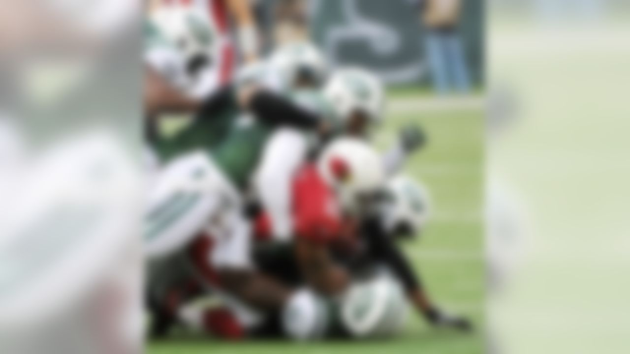 Arizona Cardinals running back Beanie Wells, center in red, is tackled by a host of New York Jets players during the first half of an NFL football game, Sunday, Dec. 2, 2012, in East Rutherford, N.J. (AP Photo/Bill Kostroun)