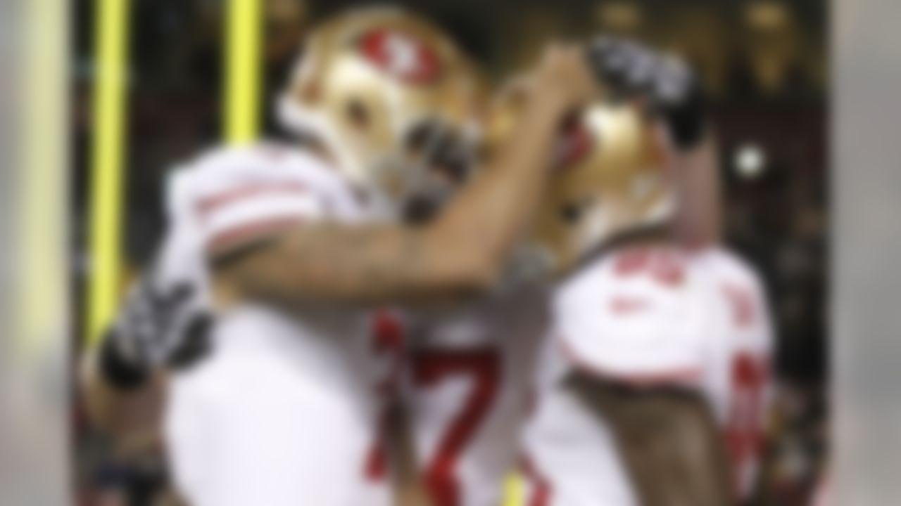 San Francisco 49ers quarterback Colin Kaepernick, left, congratulates tight end Vernon Davis on his touchdown catch during the second half of an NFL football game against the Washington Redskins in Landover, Md., Monday, Nov. 25, 2013. (AP Photo/Alex Brandon)