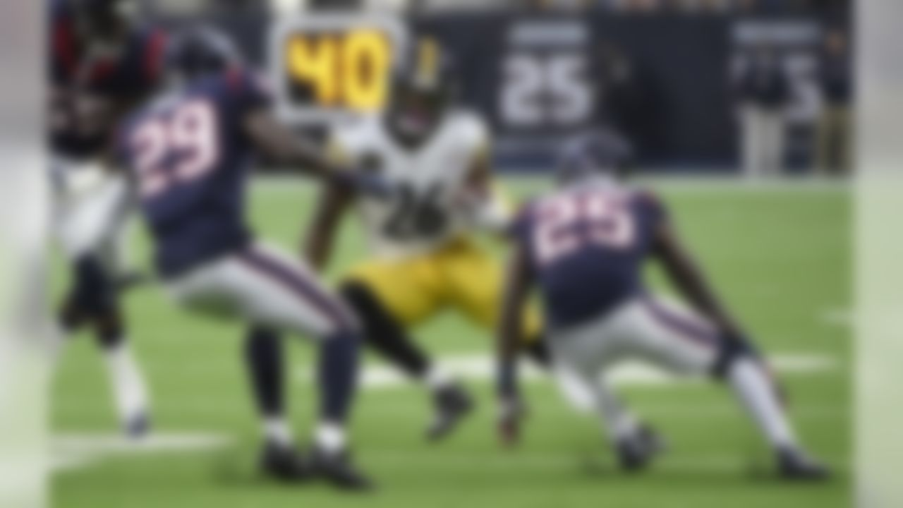 Pittsburgh Steelers running back Le'Veon Bell (26) rushes for a gain as Houston Texans' Andre Hal (29) and Kareem Jackson (25) defend during the first half of an NFL football game Monday, Dec. 25, 2017, in Houston. (AP Photo/Eric Christian Smith)
