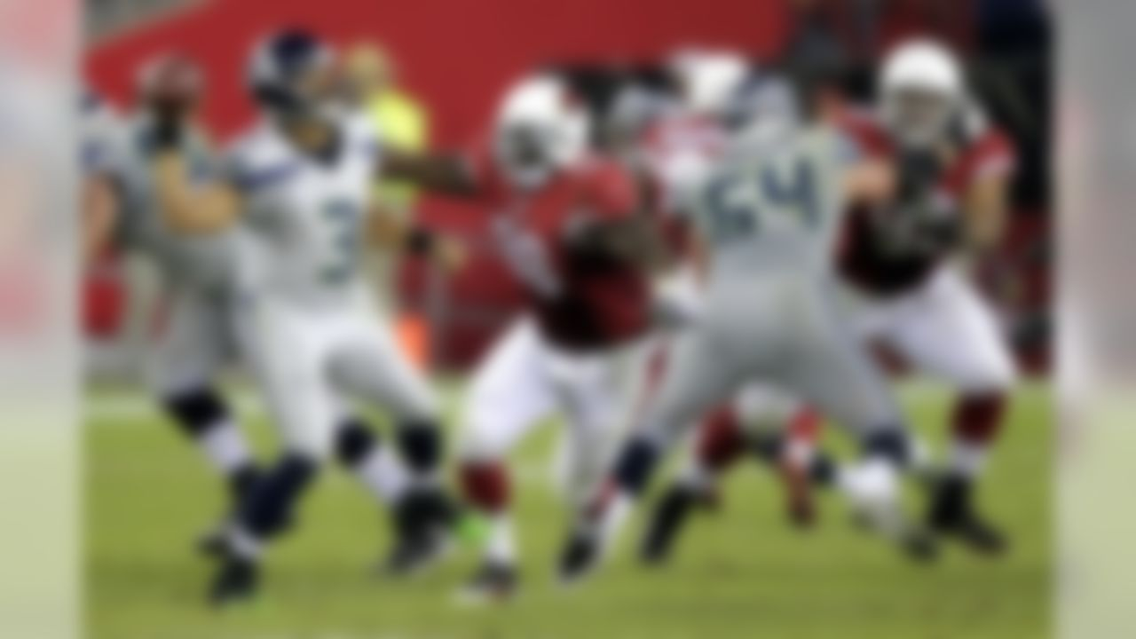 Seattle Seahawks quarterback Russell Wilson (3) throws under pressure from Arizona Cardinals defensive end Frostee Rucker (98) during the second half of an NFL football game, Thursday, Oct. 17, 2013, in Glendale, Ariz. (AP Photo/Rick Scuteri)