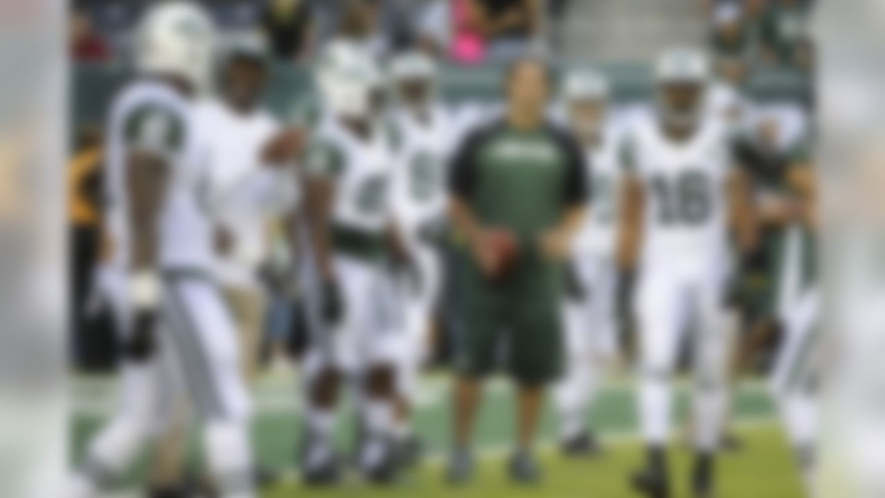 New York Jets quarterback Mark Sanchez, center, holds a football as teammates warm up before a preseason NFL football game against the Philadelphia Eagles, Thursday, Aug. 29, 2013, in East Rutherford, N.J. (AP Photo/Bill Kostroun)