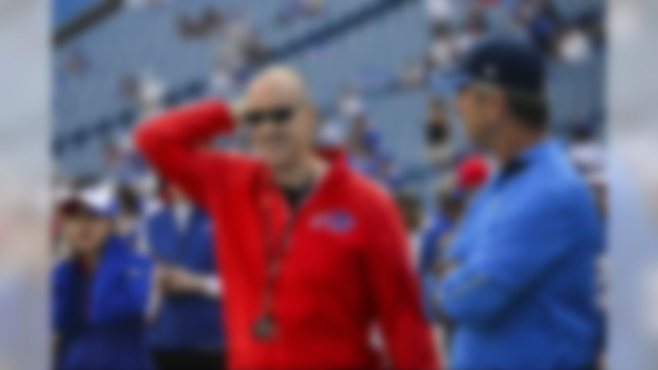 Former Buffalo Bills quarterback Jim Kelly, left, smiles as he talks to San Diego Chargers offensive coordinator Frank Reich, right, as the Buffalo Bills and the San Diego Chargers warm up for a NFL football game Sunday, Sept. 21, 2014, in Orchard Park, N.Y. (AP Photo/Gary Wiepert)