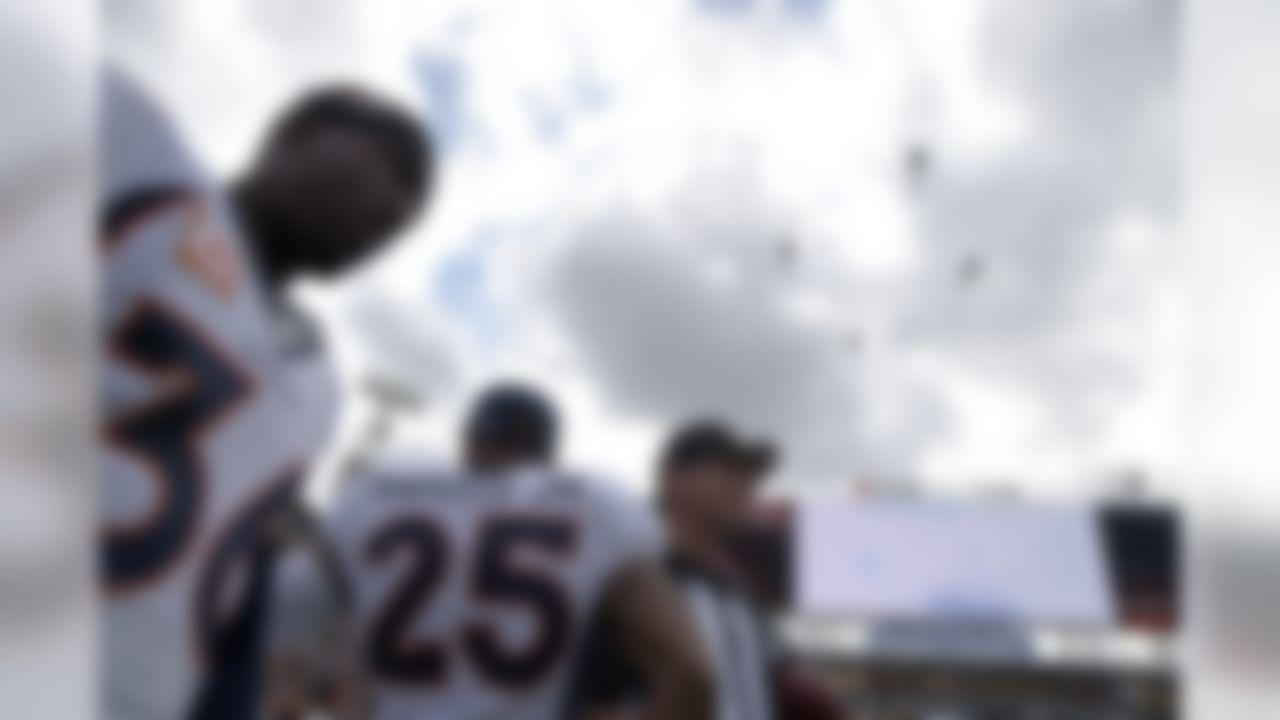 Denver Broncos cornerback Kayvon Webster (36) and cornerback Chris Harris (25) watch as U.S. Navy helicopters perform a flyover before an NFL football game against the Jacksonville Jaguars in Jacksonville, Fla., Sunday, Dec. 4, 2016. (AP Photo/Phelan M. Ebenhack)