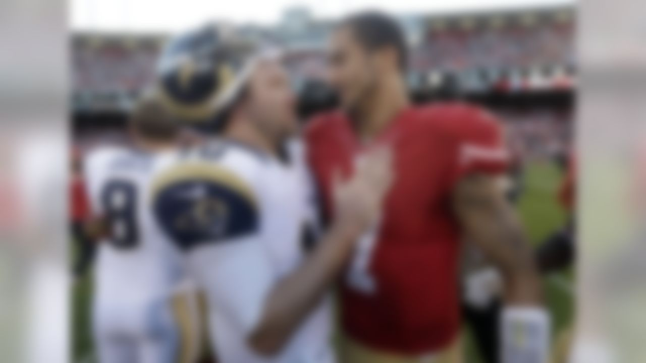 St. Louis Rams quarterback Kellen Clemens, left, talks with San Francisco 49ers quarterback Colin Kaepernick after an NFL football game in San Francisco, Sunday, Dec. 1, 2013. The 49ers won 23-13. (AP Photo/Marcio Jose Sanchez)