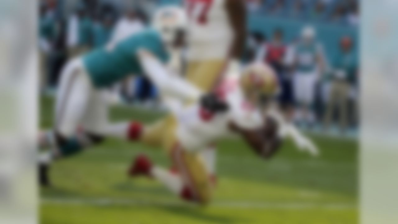 San Francisco 49ers running back Carlos Hyde (28) falls into the end zone for a touchdown as Miami Dolphins cornerback Byron Maxwell (41) is late with the tackle, during the first half of an NFL football game, Sunday, Nov. 27, 2016, in Miami Gardens, Fla. (AP Photo/Lynne Sladky)
