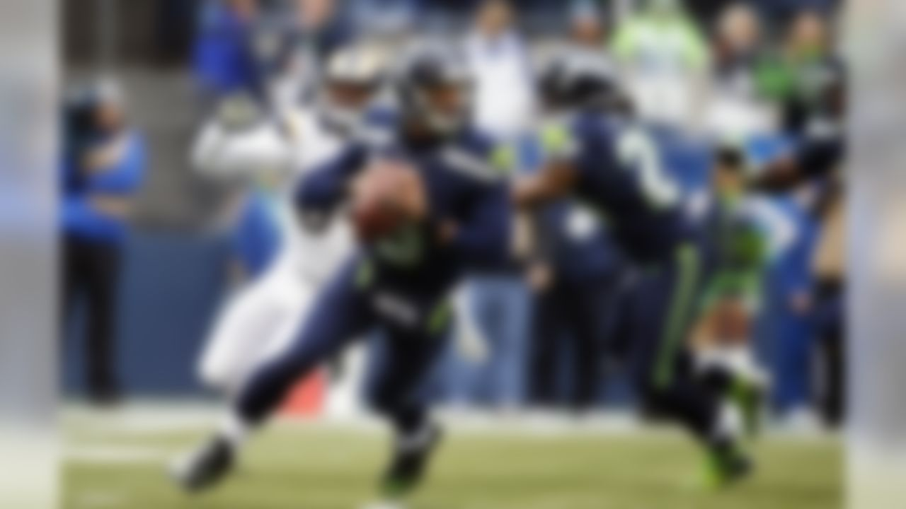 Seattle Seahawks quarterback Russell Wilson drops to pass against the St. Louis Rams in the first half of an NFL football game, Sunday, Dec. 29, 2013, in Seattle. (AP Photo/John Froschauer)